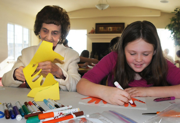Helen Magness, left, with Coyote Ridge Elementay School 4th grader, Abbey Nicol make a Thanksgiving centerpiece for the residents of  Highland Trail Highland Trail independent-living retirement community on Friday. <br /> November 20, 2009<br /> Staff photo/David R. Jennings