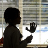 Fourth grader Kyra Mowry, Coyote Ridge Elementay School, is silhouetted against a window while holding a paper turkey for a centerpiece she made with a resident of  Highland Trail Highland Trail independent-living retirement community on Friday. <br /> November 20, 2009<br /> Staff photo/David R. Jennings