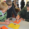 Jack Czernicki, right, makes an outline of the hand of Coyote Ridge Elementay School 4th grader Matt Ray, center, while Camden Brown watches as they  make a Thanksgiving centerpiece for the residents of  Highland Trail Highland Trail independent-living retirement community on Friday. <br /> November 20, 2009<br /> Staff photo/David R. Jennings