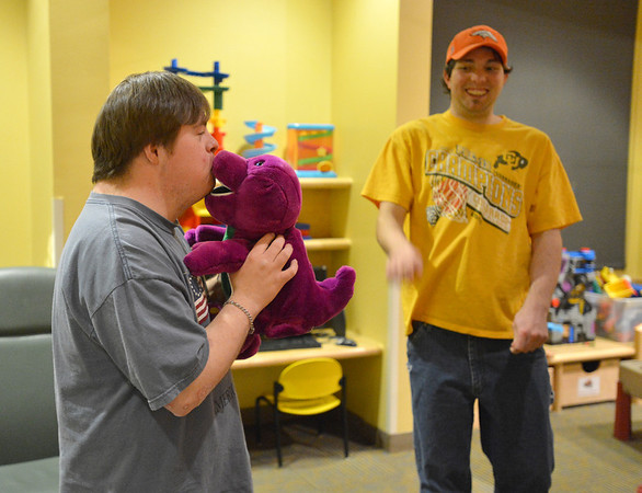 Kyle Cecil, left, kisses a Barney doll as Luke Langston watches during Game Night at the Derda Recreation Center on Saturday.<br /> January 19, 2013<br /> staff photo/ David R. Jennings