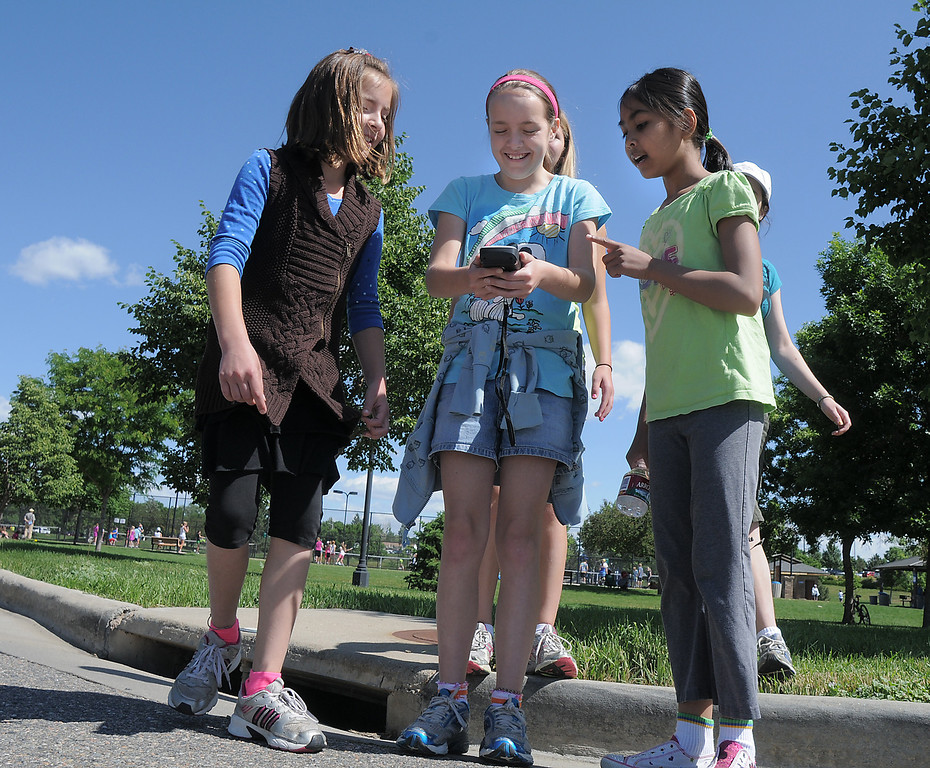 Gwen Lewis, 11, center, holds a GPS instrument with Paige Lewis, 11, left, and, Sarita Maharajh, 10, as they try to figure out which direction to go as they search for  locations during the Mamie Doud Eisenhower Public Library's Geocache Planet Race for teens at Community Park on Tuesday.<br /> June 21, 2011<br /> staff photo/David R. Jennings