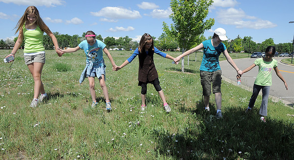 Sarah Carvo, 11, left, Gwen Lewis, 11, Paige Lewis, 11, Skye Lewis, 16, and Sarita Maharajh, 10, form a line to search for a GPS location  during the Mamie Doud Eisenhower Public Library's Geocache Planet Race for teens at Community Park on Tuesday. June 21, 2011 staff photo/David R. Jennings