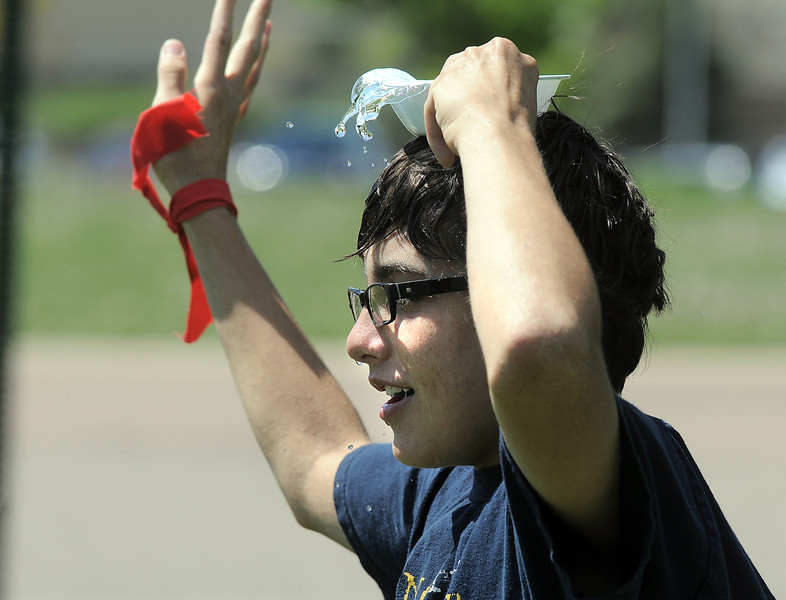 Paris Sitchler, 14, tries carrying water on his head during a game at the Mamie Doud Eisenhower Public Library's Geocache Planet Race for teens at Community Park on Tuesday.<br /> June 21, 2011<br /> staff photo/David R. Jennings