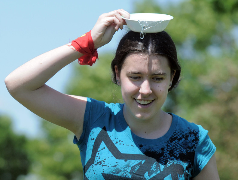 Skye Lewis, 16,  tries carrying water in a dish on her head during a game at the Mamie Doud Eisenhower Public Library's Geocache Planet Race for teens at Community Park on Tuesday.<br /> June 21, 2011<br /> staff photo/David R. Jennings