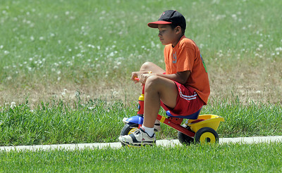 C. J. Gomez, 12,rides a tricycle around a course for the Martian lander station  during the Mamie Doud Eisenhower Public Library's Geocache Planet Race for teens at Community Park on Tuesday. June 21, 2011 staff photo/David R. Jennings