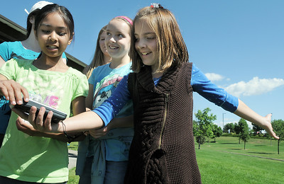 Paige Lewis, 11, holds a GPS instrument with help from Sarita Maharajh, 10, left, and Gwen Lewis, 11, as they try to figure out which direction to go to find the planet Saturn location during the Mamie Doud Eisenhower Public Library's Geocache Planet Race for teens at Community Park on Tuesday. June 21, 2011 staff photo/David R. Jennings