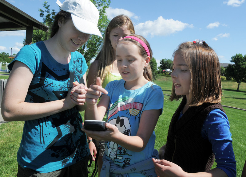 Gwen Lewis, 11, center, holds a GPS device, tries to figure out which direction to travel with her sisters Syke, 16, left, Paige, 11, right, and Sarah Carvo, 11, during the Mamie Doud Eisenhower Public Library's Geocache Planet Race for teens at Community Park on Tuesday.<br /> June 21, 2011<br /> staff photo/David R. Jennings