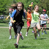 "Paige Lewis, 11, runs as ""asteroids' are being thrown at her team during the asteroid gantlet at Mamie Doud Eisenhower Public Library's Geocache Planet Race for teens at Community Park on Tuesday.<br /> June 21, 2011<br /> staff photo/David R. Jennings"