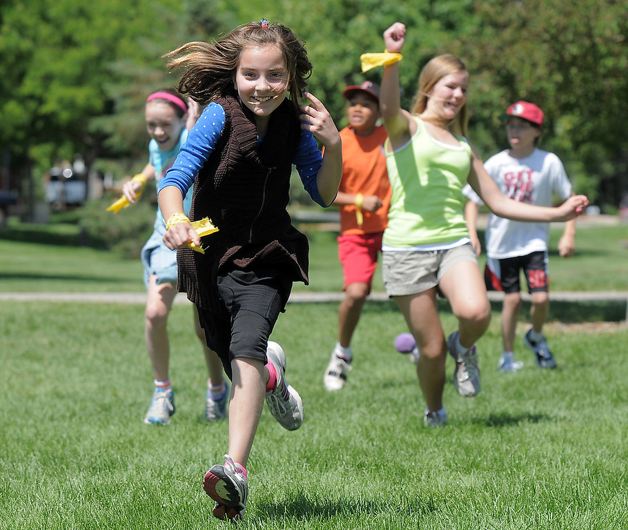 """Paige Lewis, 11, runs as """"asteroids' are being thrown at her team during the asteroid gantlet at Mamie Doud Eisenhower Public Library's Geocache Planet Race for teens at Community Park on Tuesday.<br /> June 21, 2011<br /> staff photo/David R. Jennings"""