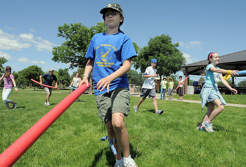 Sara Hollister, 13, runs to tag a participant during the solar flair tag game at Mamie Doud Eisenhower Public Library's Geocache Planet Race for teens at Community Park on Tuesday.<br /> June 21, 2011<br /> staff photo/David R. Jennings