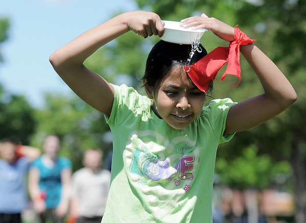 Sarita Maharajh, 10,  tries carrying water in a dish on her head during a game at the Mamie Doud Eisenhower Public Library's Geocache Planet Race for teens at Community Park on Tuesday.<br /> June 21, 2011<br /> staff photo/David R. Jennings