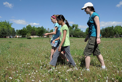 Gwen Lewis, 11, left, leads Sarita Maharajh, 10, and Skye Lewis, 16, as they search for GPS locations during the Mamie Doud Eisenhower Public Library's Geocache Planet Race for teens at Community Park on Tuesday. June 21, 2011 staff photo/David R. Jennings