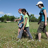 Gwen Lewis, 11, left, leads Sarita Maharajh, 10, and Skye Lewis, 16, as they search for GPS locations during the Mamie Doud Eisenhower Public Library's Geocache Planet Race for teens at Community Park on Tuesday.<br /> June 21, 2011<br /> staff photo/David R. Jennings