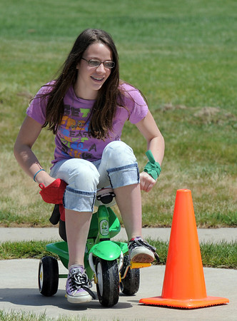 Gwen Mulligan, 14, rides a tricycle around a course for the Martian lander station during the Mamie Doud Eisenhower Public Library's Geocache Planet Race for teens at Community Park on Tuesday.<br /> June 21, 2011<br /> staff photo/David R. Jennings