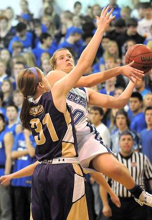 Broomfield's Meagan Prins goes to the basket against Holy Family's Kassie Johannsen during Saturday's cross-town rivalry game at Broomfield.<br /> January 28, 2012<br /> staff photo/ David R. Jennings