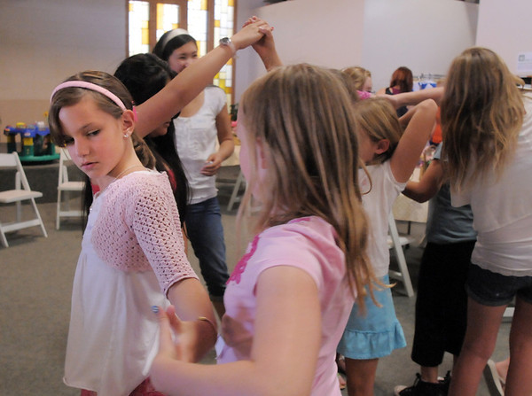 Shelby Horne, 9, left, works with Joy Putnam, 10, and others in the group to try and get untangled without breaking their hold during the girls self esteem workshop led by Gracie Forrey on Tuesday at Broomfield United Methodist Church.<br /> July 26, 2011<br /> staff photo/ David R. Jennings