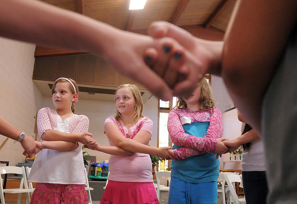 Shelby Horne,9, left, Joy Putnam, 10, and Corinne Neustadter, 10, hold hands in their group for an exercise during the girls self esteem workshop led by Gracie Forrey on Tuesday at Broomfield United Methodist Church.<br /> July 26, 2011<br /> staff photo/ David R. Jennings