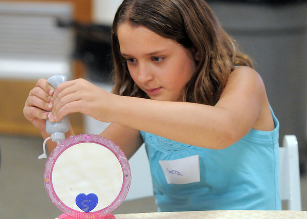Sierra Schottenloher-Brent, 11, puts glitter on her mirror during the girls self esteem workshop led by Gracie Forrey on Tuesday at Broomfield United Methodist Church.<br /> July 26, 2011<br /> staff photo/ David R. Jennings