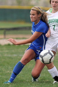Broomfield's Hailey Mazzola moves the ball away from Niwot's Lauren Tatusko during Thursday's game at Niwot.  April 19, 2012  staff photo/ David R. Jennings