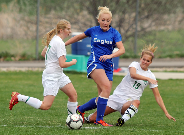 Broomfield's Sara Barton fights for control of the ball with Niwot's Lauren Tatusko, left, and Samantha Shaner during Thursday's game at Niwot.<br /> <br /> April 19, 2012 <br /> staff photo/ David R. Jennings