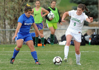 Niwot's Lauren FitzGibbons moves the ball past Broomfield's Kerri Marquardt during Thursday's game at Niwot.  April 19, 2012  staff photo/ David R. Jennings