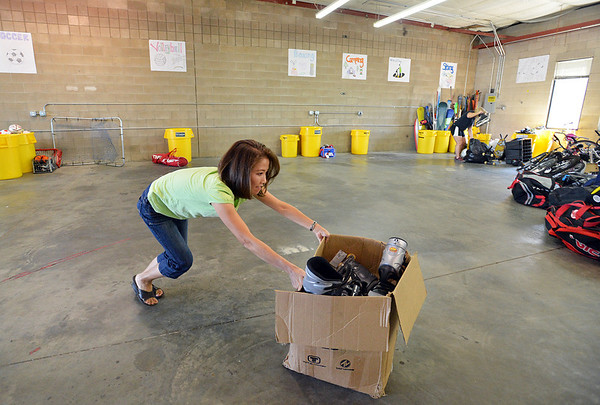 Judy Carmosino pushes a box of sports gear across the floor while helping unload a semi truck from Ball Corp. with 5,000 cubic feet of sports equipment for the Jessica Redfield Ghawi giveSports Scholarship Fund at A Precious Child on Saturday.<br /> September 8, 2012<br /> staff photo/ David R. Jennings