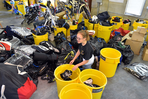 Jeanie Cox, 13, helps sort hockey equipment unloaded from a semi truck from Ball Corp. with 5,000 cubic feet of sports equipment for the Jessica Redfield Ghawi giveSports Scholarship Fund at A Precious Child on Saturday.<br /> September 8, 2012<br /> staff photo/ David R. Jennings