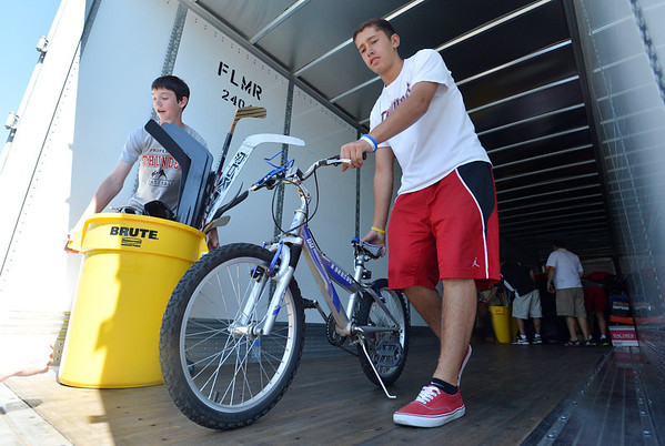 Griffin Hellar, 14, left, and Isaiah Pierotti, 13, move sports gear out of the semi truck from Ball Corp. with 5,000 cubic feet of sports equipment for the Jessica Redfield Ghawi giveSports Scholarship Fund at A Precious Child on Saturday.<br /> September 8, 2012<br /> staff photo/ David R. Jennings
