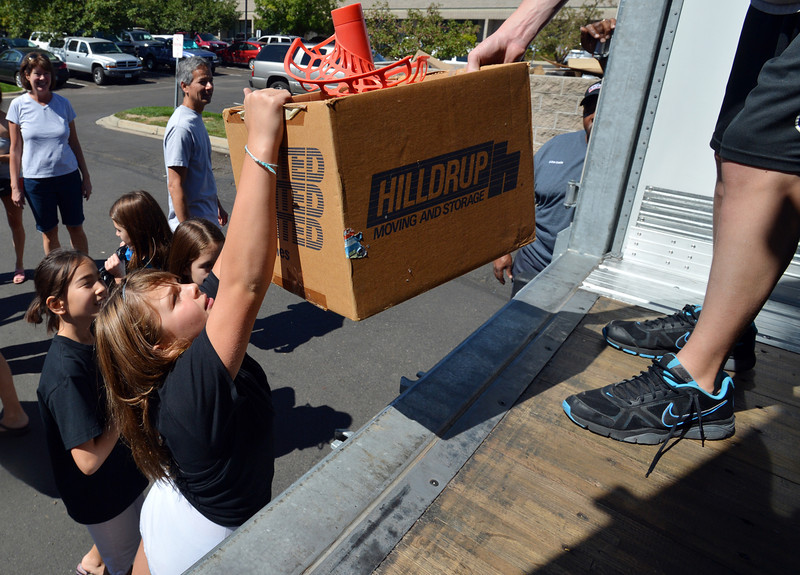 Lauren Ferraro, 10, reaches for a box full of sports gear while helping unload a semi truck from Ball Corp. with 5,000 cubic feet of sports equipment for the Jessica Redfield Ghawi giveSports Scholarship Fund at A Precious Child on Saturday.<br /> September 8, 2012<br /> staff photo/ David R. Jennings