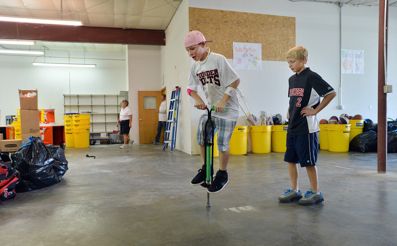 Zane Zinicola, 10,  jump on a pogo stick as Jonah Cox, 11, watches, right, while helping unload a semi truck from Ball Corp. with 5,000 cubic feet of sports equipment for the Jessica Redfield Ghawi giveSports Scholarship Fund at A Precious Child on Saturday.<br /> September 8, 2012<br /> staff photo/ David R. Jennings