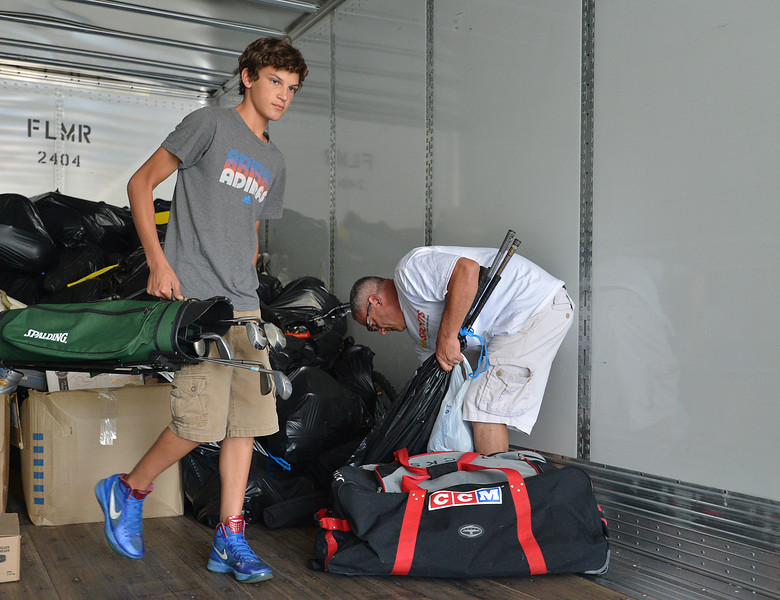 Griffin Hellar, 14, left, and his father David Hellar help  unload a semi truck from Ball Corp. with 5,000 cubic feet of sports equipment for the Jessica Redfield Ghawi giveSports Scholarship Fund at A Precious Child on Saturday.<br /> September 8, 2012<br /> staff photo/ David R. Jennings
