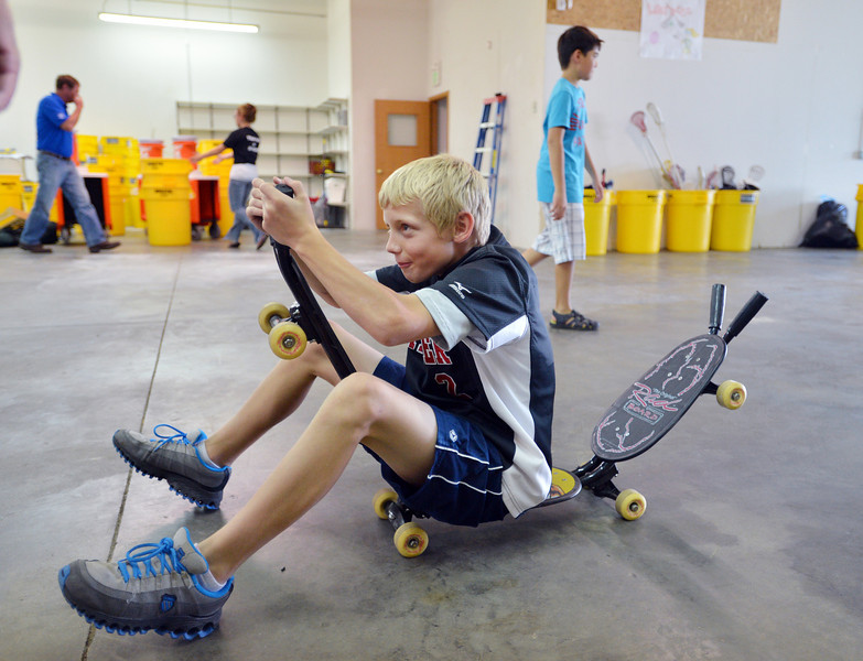 Jonah Cox, 11, rides a skate board into the storage area while helping unload a semi truck from Ball Corp. with 5,000 cubic feet of sports equipment for the Jessica Redfield Ghawi giveSports Scholarship Fund at A Precious Child on Saturday.<br /> September 8, 2012<br /> staff photo/ David R. Jennings