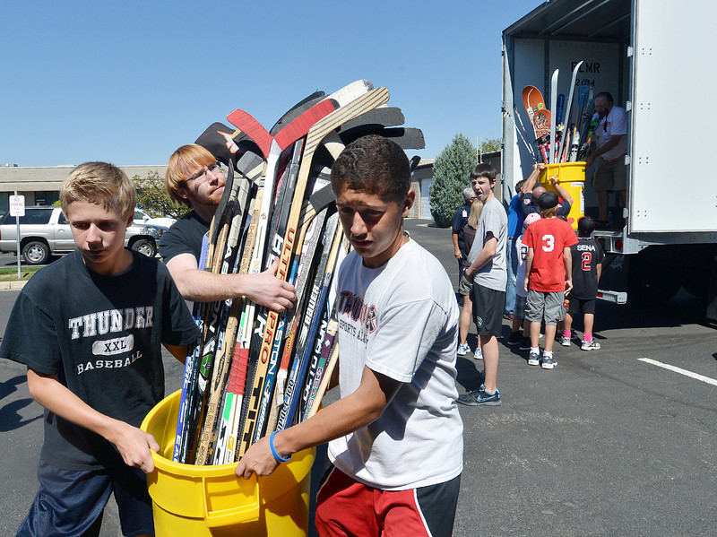 Joshua Cox, 13, left, Eric Purcell and Isaiah Pierotti, 13, carry donated hockey sticks while unloading a semi truck from Ball Corp. with 5,000 cubic feet of sports equipment for the Jessica Redfield Ghawi giveSports Scholarship Fund at A Precious Child on Saturday.<br /> September 8, 2012<br /> staff photo/ David R. Jennings