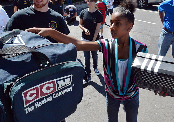Amber Horn, 14, helps unload a semi truck from Ball Corp. with 5,000 cubic feet of sports equipment for the Jessica Redfield Ghawi giveSports Scholarship Fund at A Precious Child on Saturday.<br /> September 8, 2012<br /> staff photo/ David R. Jennings