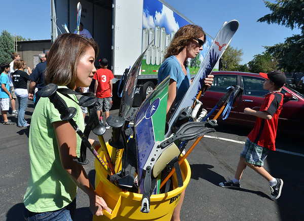 Judy Carmosino, left, and Debbie Millar carry a bin full of ski gear while unloading a semi truck from Ball Corp. with 5,000 cubic feet of sports equipment for the Jessica Redfield Ghawi giveSports Scholarship Fund at A Precious Child on Saturday.<br /> September 8, 2012<br /> staff photo/ David R. Jennings
