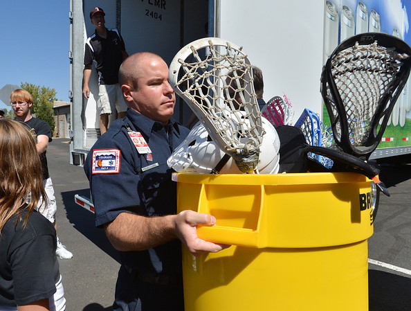 North Metro Fire Rescue firefighter David Alizer carries a bin full of lacrosse sticks while unloading a semi truck from Ball Corp. with 5,000 cubic feet of sports equipment for the Jessica Redfield Ghawi giveSports Scholarship Fund at A Precious Child on Saturday.<br /> September 8, 2012<br /> staff photo/ David R. Jennings