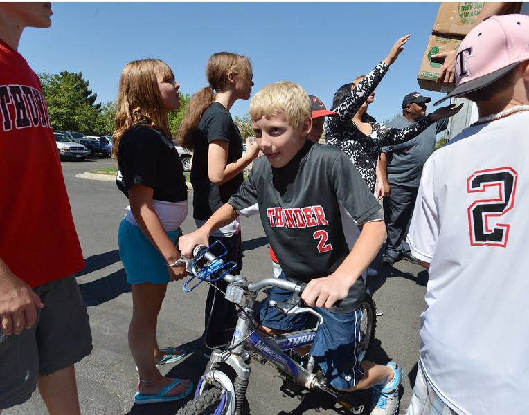 Jonah Cox, 11, rides a donated bicycle to the storage area while helping  unload a semi truck from Ball Corp. with 5,000 cubic feet of sports equipment for the Jessica Redfield Ghawi giveSports Scholarship Fund at A Precious Child on Saturday.<br /> September 8, 2012<br /> staff photo/ David R. Jennings