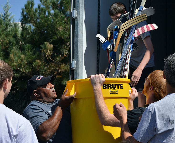 Truck driver Charles Dixon, left, and Eric Purcell lift a bin full of hockey sticks while unloading a semi truck from Ball Corp. with 5,000 cubic feet of sports equipment for the Jessica Redfield Ghawi giveSports Scholarship Fund at A Precious Child on Saturday.<br /> September 8, 2012<br /> staff photo/ David R. Jennings