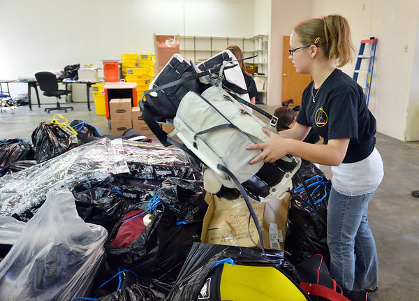 Jeanie Cox, 13, puts hokey equipment into the pile after helping  unload a semi truck from Ball Corp. with 5,000 cubic feet of sports equipment for the Jessica Redfield Ghawi giveSports Scholarship Fund at A Precious Child on Saturday.<br /> September 8, 2012<br /> staff photo/ David R. Jennings