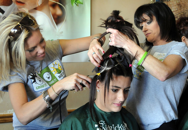 Candice Thurston has her hair is shaved off by Christina Ralston, left,  and Barb Guerrieri during the St. Baldrick's Foundation fundraiser at Papa Frank's  Restaurant on Saturday. Thurston's hair was donated to Lock of Love to make wigs for cancer patients.<br /> March 20, 2010<br /> Staff photo/David R. Jennings