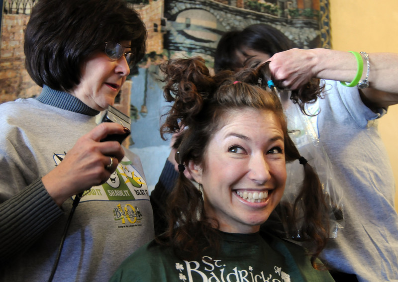 Susie Ritchey smiles as her hair is shaved by Linda Hanson, left, and Barb Guerrieri  during the St. Baldrick's Foundation fundraiser at Papa Frank's  Restaurant on Saturday. Ritchey raised over $1903 also her hair was donated to the Locks of Love to make wigs for cancer patients. Over $11,000 was raised by Papa Frank's for pediatric cancer research.<br /> <br /> March 20, 2010<br /> Staff photo/David R. Jennings