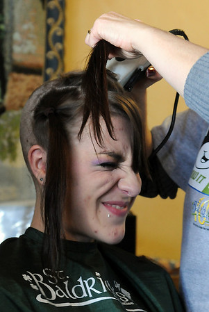 Jessica Hanson, 18, winces as her hair is shaved off by her mother Linda Hanson during the St. Baldrick's Foundation fundraiser at Papa Frank's  Restaurant on Saturday. Over $11,000 was raised for pediatric cancer research. Jessica's hair was donated to Lock of Love to make wigs for cancer patients.<br /> <br /> March 20, 2010<br /> Staff photo/David R. Jennings