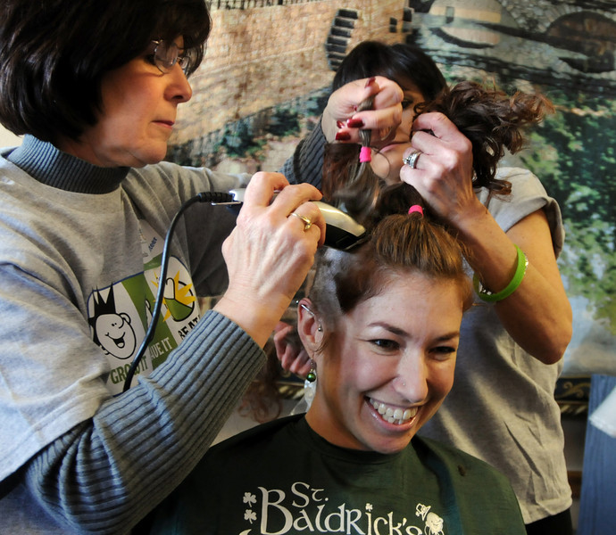 Susie Ritchey hair is shaved by Linda Hanson and Barb Guerrieri  during the St. Baldrick's Foundation fundraiser at Papa Frank's  Restaurant on Saturday. <br /> <br /> March 20, 2010<br /> Staff photo/David R. Jennings