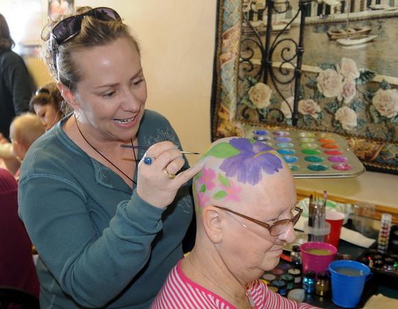 Artist Tiffany Koehn paints flowers on the head of cancer patient Kathy Linendoll during the St. Baldrick's Foundation fundraiser at Papa Frank's  Restaurant on Saturday. <br /> March 20, 2010<br /> Staff photo/David R. Jennings