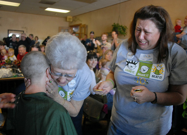 Susie Ritchey is hugged by her grandmother Dorothy Rizzi while her mother Cindy Ritchey cries after Susie's hair was shaved off for the St. Baldrick's Foundation fundraiser at Papa Frank's  Restaurant on Saturday. Susie organized the event that raised over $11,000 for pediatric cancer research.<br /> <br /> March 20, 2010<br /> Staff photo/David R. Jennings