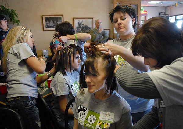 Candice Thurston, center left, and Jessica Hanson, 18, center right, have their hair prepared to be shaved off by beauticians from Chateau Salon and donated to Locks of Love during the the St. Baldrick's Foundation fundraiser at Papa Frank's  Restaurant on Saturday. <br /> <br /> March 20, 2010<br /> Staff photo/David R. Jennings