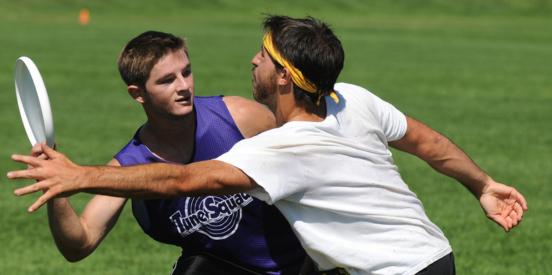 "Matty Zemel, left, ""Sleeveless"" looks for an opening to throw around Zach Nager, ""Blue"" during the Grass Roots Ultimate Frisbee tournament at Broomfield County Commons Park on Saturday.<br /> August 21, 2010<br /> staff photo/David R. Jennings"