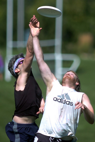 "Scott Potter, left, ""Sleevless"", and Tim Matthews, ""Blue""  reach for the frisbee during the Grass Roots Ultimate Frisbee tournament at Broomfield County Commons Park on Saturday.<br /> August 21, 2010<br /> staff photo/David R. Jennings"