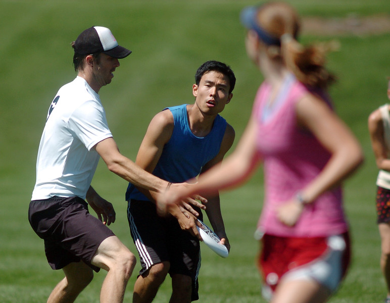 "Jeffery Lou, center,  ""Sleeveless"", looks for an open teammate to throw to during the Grass Roots Ultimate Frisbee tournament at Broomfield County Commons Park on Saturday.<br /> August 21, 2010<br /> staff photo/David R. Jennings"