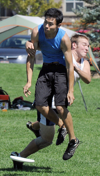 "Jeffery Lou, left,  ""Sleeveless"", collides with another player during the Grass Roots Ultimate Frisbee tournament at Broomfield County Commons Park on Saturday.<br /> August 21, 2010<br /> staff photo/David R. Jennings"